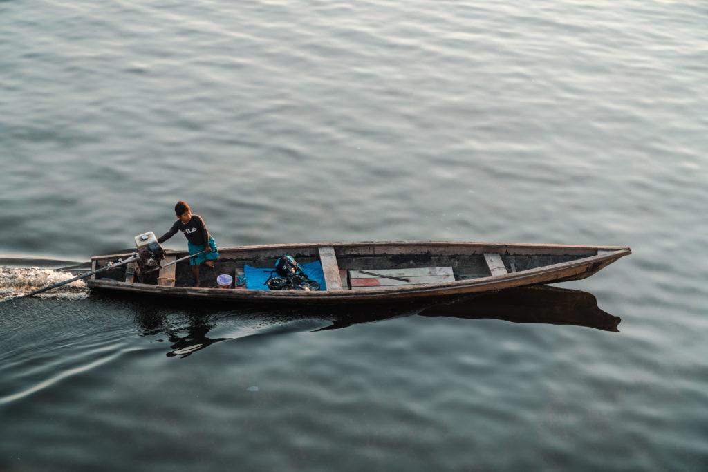 Fischerboote fahren am Frachtschiff auf dem Amazonasvorbei